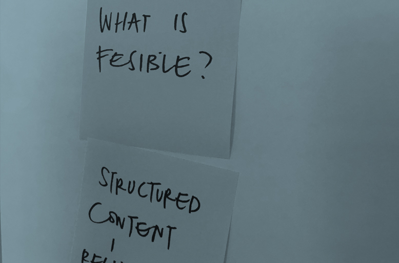 Post-it on whiteboard with words 'what is feasible' and 'structured content' visible